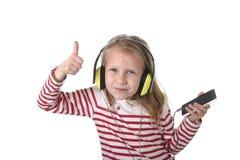 Petite fille douce avec les cheveux blonds écoutant la musique avec les écouteurs et le téléphone portable heureux Photographie stock