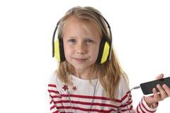 Petite fille douce avec les cheveux blonds écoutant la musique avec les écouteurs et le téléphone portable heureux Photos stock