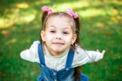 Petite fille douce dehors avec les cheveux bouclés dans des deux longues queues, portret de plan rapproché Images stock