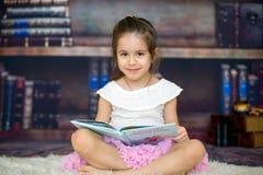 Petite fille douce, lisant un livre à la maison Images stock