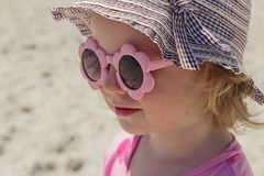 Petite fille drôle 3 années à la mer dans des lunettes de soleil roses images stock