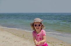 Petite fille drôle 3 années à la mer dans des lunettes de soleil roses photos libres de droits