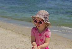 Petite fille drôle 3 années à la mer dans des lunettes de soleil roses photo libre de droits