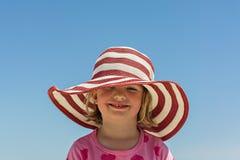 Petite fille drôle 4 années en mer dans un grand chapeau rayé images libres de droits