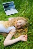 Petite fille drôle avec l'ordinateur portatif à l'extérieur Photographie stock
