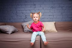 Petite fille drôle choyant et jouant sur les talons de Sofa At Home Showing Naked Il rit montrant sa langue et dents Elle est Dr. Photographie stock