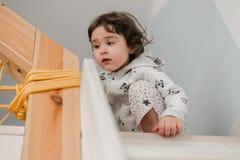 Petite fille drôle dans des pijamas mignons ayant l'amusement photo stock