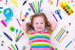 Petite fille drôle avec des fournitures scolaires Photo libre de droits