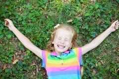 Petite fille drôle avec l'oeil fermé se trouvant sur l'herbe Image libre de droits