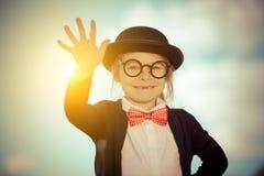 Petite fille drôle dans le chapeau de noeud papillon et de lanceur avec bonjour le geste images libres de droits