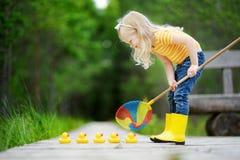 Petite fille drôle jouant avec cinq canetons en caoutchouc photo stock