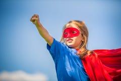 Petite fille drôle jouant le superhéros de puissance Photographie stock