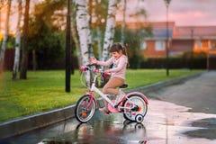Petite fille drôle sur un vélo Photographie stock libre de droits