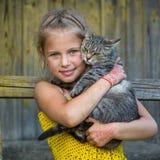 Petite fille drôle tenant un chat dans des ses bras Amour Photographie stock libre de droits