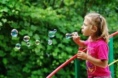 Petite fille effectuant des bulles de savon images stock