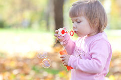 Petite fille effectuant le ventilateur de bulle sur la forêt d'automne Photo stock