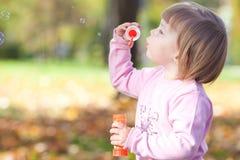 Petite fille effectuant le ventilateur de bulle sur la forêt d'automne Image libre de droits