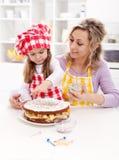 Petite fille effectuant son premier gâteau de fruit Photographie stock libre de droits