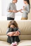 Petite fille effrayée écoutant l'argument de parents Photographie stock libre de droits