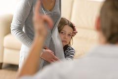 Petite fille effrayée se cachant derrière sa mère Image stock
