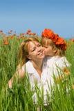 Petite fille embrassant sa mère sur la zone de pavot Photographie stock libre de droits