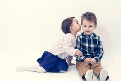 Petite fille embrassant son frère plus âgé sur la joue Photo stock