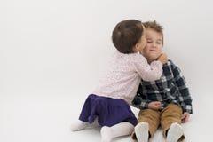 Petite fille embrassant son frère plus âgé sur la joue Images libres de droits
