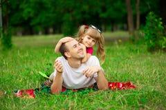 Petite fille embrassant son père pendant la promenade en parc Photos libres de droits