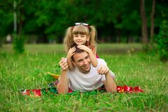 Petite fille embrassant son père pendant la promenade en parc Images libres de droits