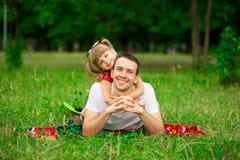 Petite fille embrassant son père pendant la promenade en parc Photo stock