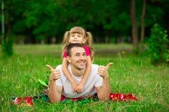 Petite fille embrassant son père pendant la promenade en parc Image stock