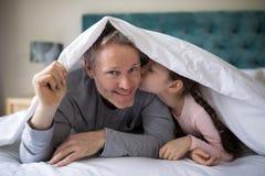 Petite fille embrassant son père sur le poussin dans la chambre à coucher Image stock