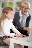 Petite fille employant le regard de grand-maman étonné par ordinateur portable Photographie stock