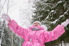 Petite fille en flocons de neige contagieux de veste rose en parc d'hiver Image libre de droits