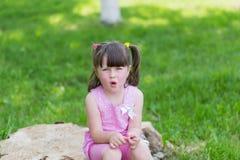 Petite fille en parc sur un tronçon Image stock