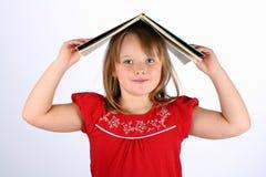 Petite fille en rouge retenant un livre sur sa tête Image stock