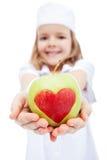 Petite fille en tant qu'infirmière te donnant une pomme Image stock