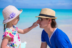 Petite fille enduisant la crème de protection de Sun du nez de son papa Photo libre de droits