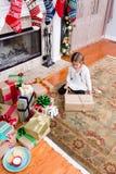 Petite fille enveloppant des cadeaux de Noël à la maison photos libres de droits