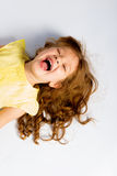 Petite fille espiègle dans rire jaune de robe Photos stock
