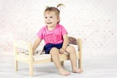 Petite fille espiègle s'asseyant sur le petit lit en bois Photo libre de droits