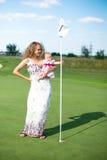 Petite fille essayant d'entrer la boule de golf dans photographie stock libre de droits