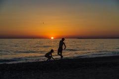 Petite fille et adolescent jouant sur une plage au coucher du soleil photo stock