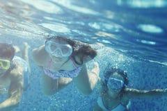 Petite fille et amis ayant l'amusement dans la piscine Photographie stock libre de droits