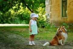 Petite fille et chien pour une promenade Images stock