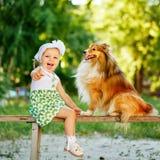 Petite fille et chien se reposant sur un banc Photos stock