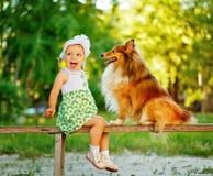 Petite fille et chien se reposant sur un banc Images stock