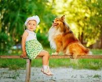 Petite fille et chien se reposant sur un banc Photos libres de droits