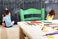 Petite fille et dessin et peinture mignons de garçon au jardin d'enfants Club créatif d'enfants d'activités photographie stock libre de droits