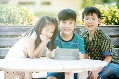 Petite fille et garçon asiatiques s'asseyant sur la longue chaise en bois utilisant le chiffre Photographie stock